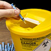 A needle being placed in a sharps container
